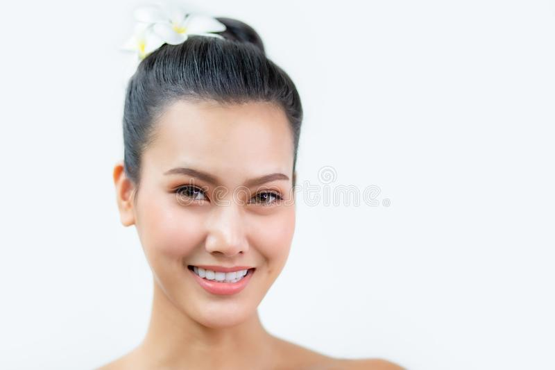 Beauty asian Woman face and Clean skin with Orchid on hair . close up beautiful girl smiling with makeup , cosmetic . portrait royalty free stock photo