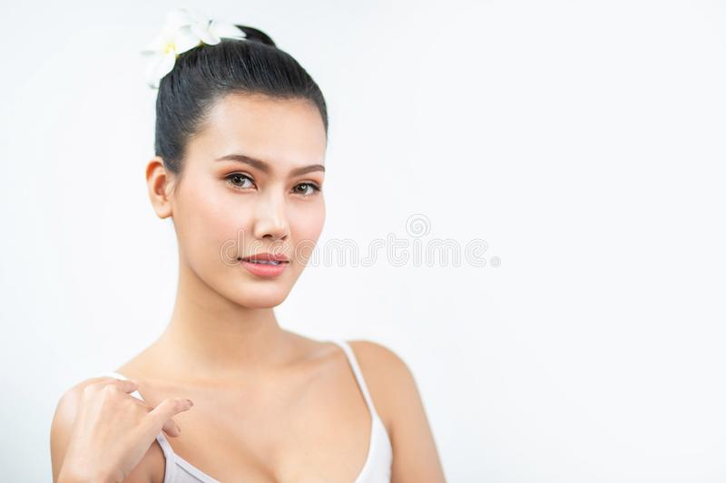 Beauty asian Woman face and Clean skin with Orchid on hair . close up beautiful girl smiling with makeup , cosmetic . portrait stock photo