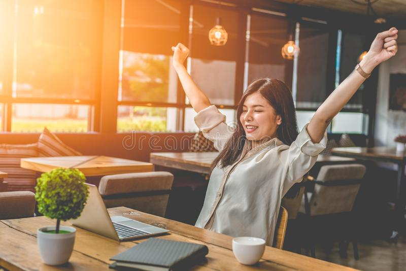 Beauty Asian woman raising two hands after finishing job happily. With laptop computer. People and lifestyles concept. Technology and Business working theme stock photos