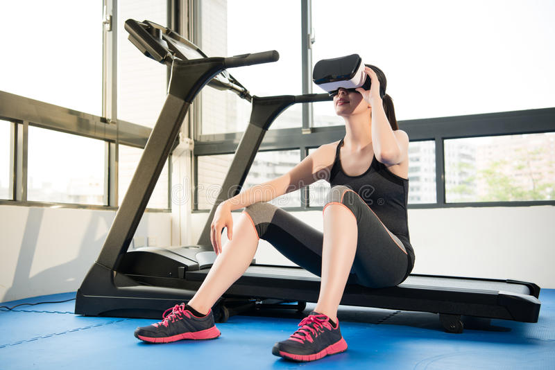Beauty asian woman rest on treadmill with VR headset. Beauty asian woman rest on treadmill with virtual reality. VR headset glasses device. indoors gym stock photo