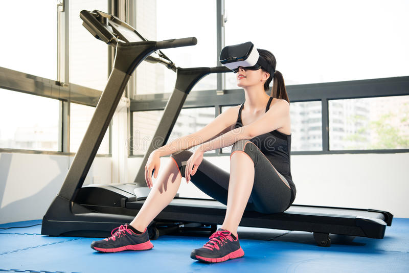 Beauty asian woman rest on treadmill with VR headset. Beauty asian woman rest on treadmill with virtual reality. VR headset glasses device. indoors gym royalty free stock photography
