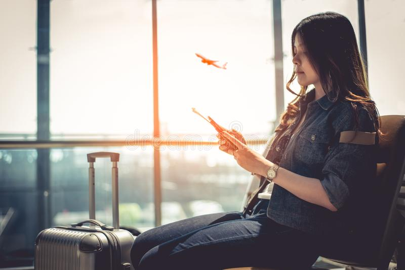 Beauty Asian woman with suitcase luggage waiting for departure while using smart phone in airport lounge. Female traveler and. Tourist theme. High season and royalty free stock photos