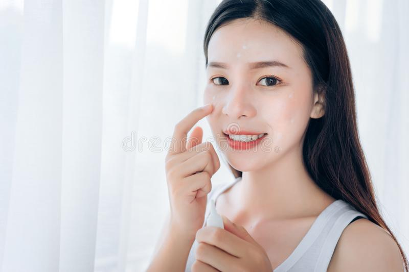 Beauty Asian Woman use Acne Gel Skincare after Cleansing royalty free stock image