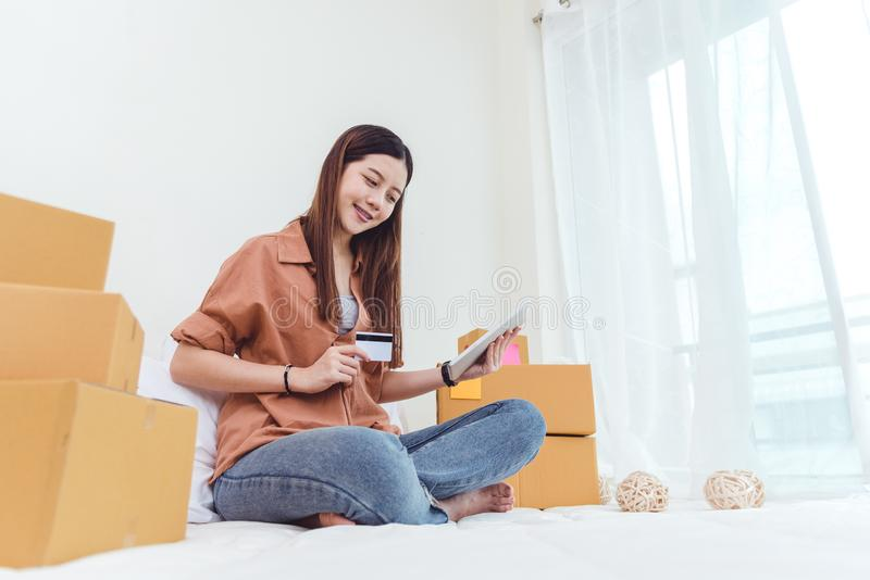 Beauty Asian woman using tablet and credit card. Start up small business entrepreneur SME and checking order list in bedroom, stock photo
