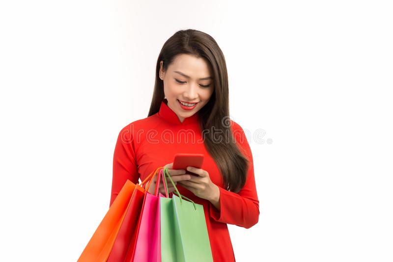 Beauty asian woman with Vietnamese dress, chinese new year using smartphone technology shopping online and hold bag stock photos