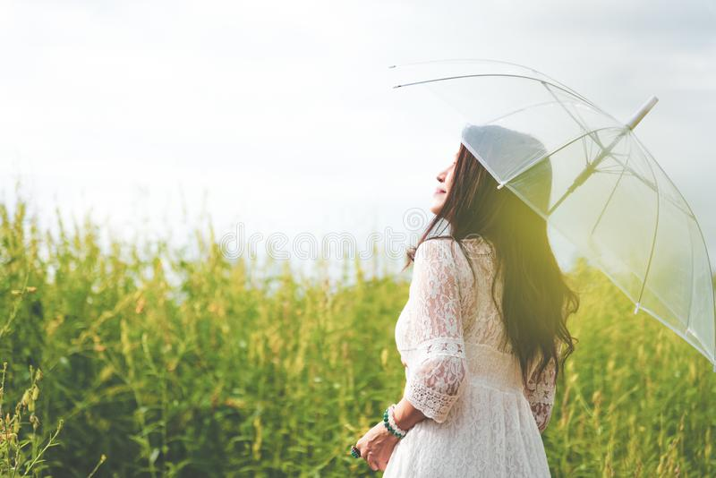 Beauty Asian woman in white dress holding transparent umbrella and look at sky between rapeseed flower field background. People royalty free stock photos
