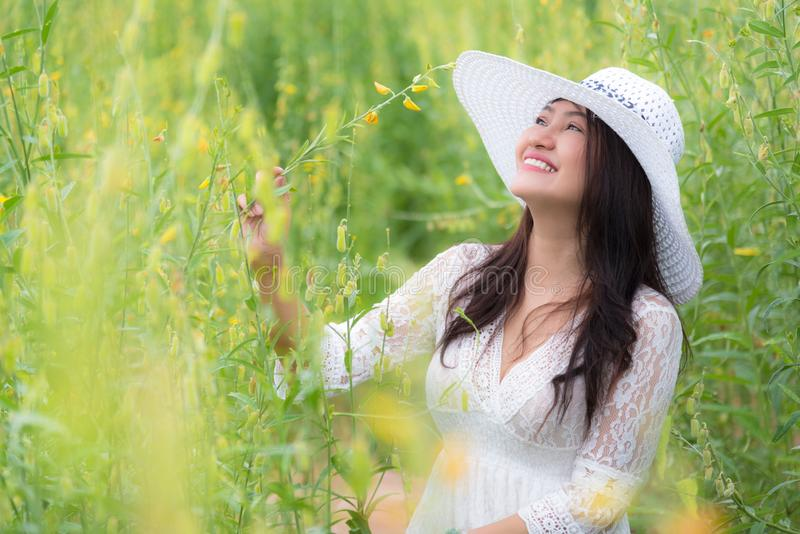 Beauty Asian woman in white dress and wing hat walking in rapeseed flower field background. Relaxation and travel concept. royalty free stock images