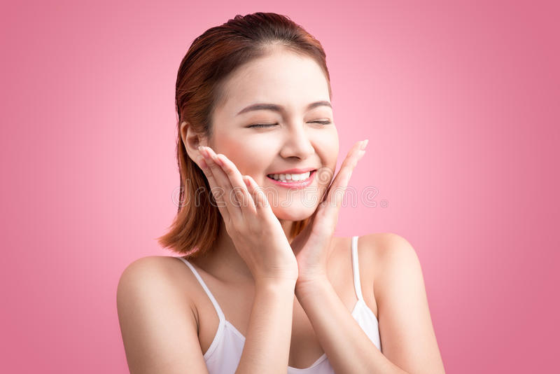 Beauty Asian Young Portrait. Beautiful Spa Woman Touching her Fa. Ce. Perfect Fresh Skin. Pure Beauty Model Girl On Pink Background stock photography