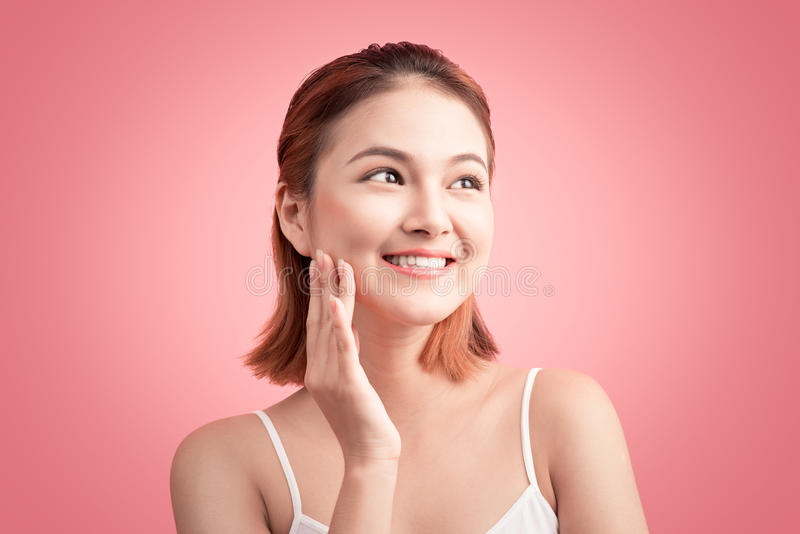 Beauty Asian Young Portrait. Beautiful Spa Woman Touching her Fa. Ce. Perfect Fresh Skin. Pure Beauty Model Girl On Pink Background royalty free stock image