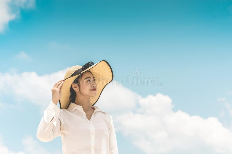 Beauty Attractive Asian woman wearing white shirt and hat relax looking up to the blue sky smile and happiness in summer vacations royalty free stock image