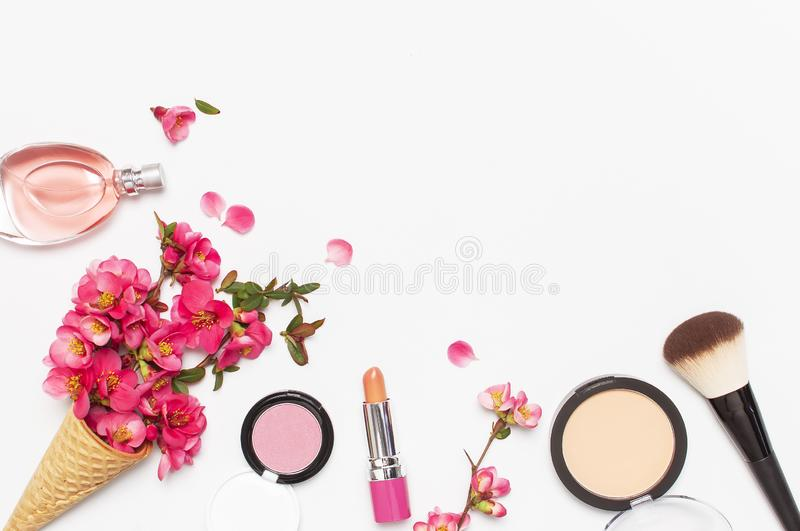 Beauty background. Waffle cone with pink spring flowers and different makeup cosmetic on light background. Face powder lipstick royalty free stock photo