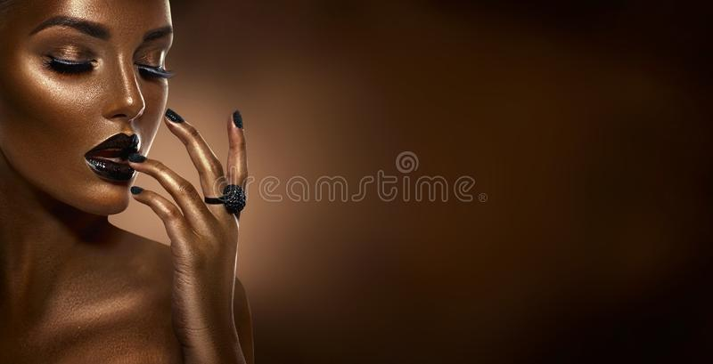 Beauty black girl fashion art portrait over dark brown background. Professional makeup and manicure. Afro American young woman with beautiful skin. Chocolate stock photo