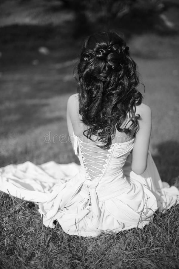 Beauty black and white portrait. Brunette bride resting and sitting on green grass at spring park. stock photos