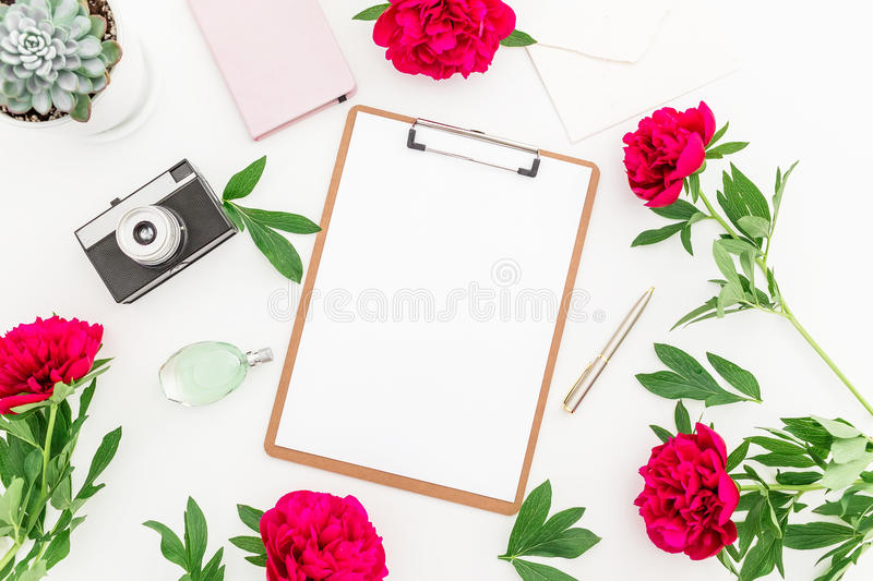 Beauty blog concept. Blogger or freelancer workspace with clipboard, notebook, retro camera, peonies and coffee mug on white backg royalty free stock image