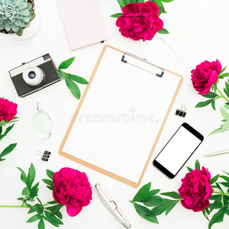 Beauty blog concept. Blogger or freelancer workspace with clipboard, notebook, retro camera, peonies and mobile phone on white bac stock photo