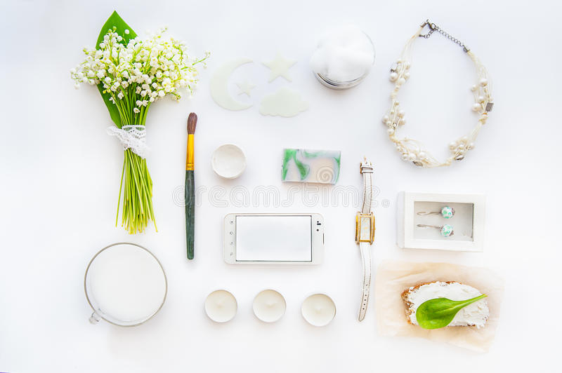 Beauty blog concept. Female styled accessories: smartfone, watches, necklace, cosmetic and bouquet of may-lily flowers on white ba royalty free stock photography