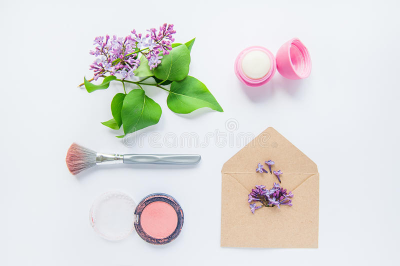 Beauty blog concept. Few female styled accessories: lips balm, rouge and brush, kraft envelope with lilac and lilac flowers sprig royalty free stock photos