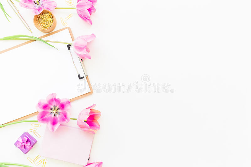 Beauty blog concept. Freelancer or blogger workspace with clipboard, notebook, pink tulips and accessories on white background. Fl royalty free stock photography