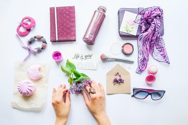 Beauty blog concept. Lilac colour. Female hands keep lilac flower among styled accessories: sunglasses, bijouterie, cosmetics and royalty free stock photography