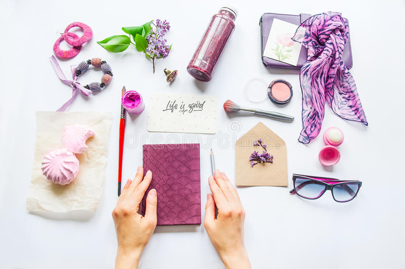 Beauty blog concept. Lilac colour. Female hands on the notebook among styled accessories: sunglasses, bijouterie, cosmetics and li royalty free stock image