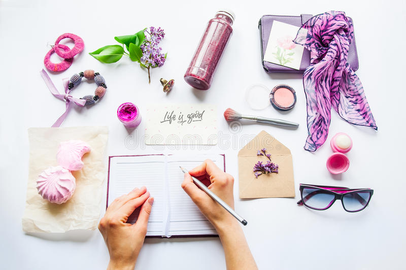 Beauty blog concept. Lilac colour. Female hands writing in notebook among styled accessories: sunglasses, bijouterie, cosmetics an stock image
