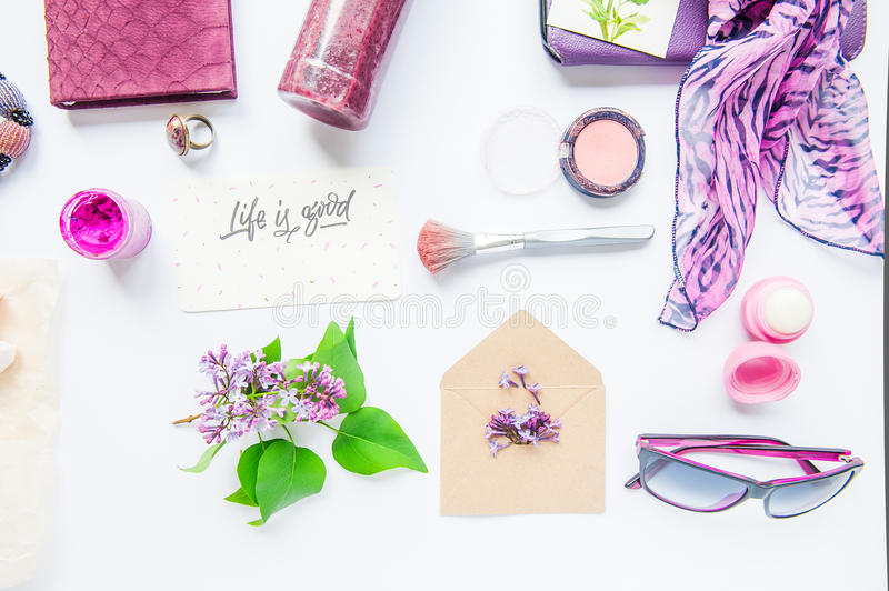 Beauty blog concept. Lilac colour. Female styled accessories: notebook, sunglasses, bijouterie items, cosmetics and lilac flowers stock photos