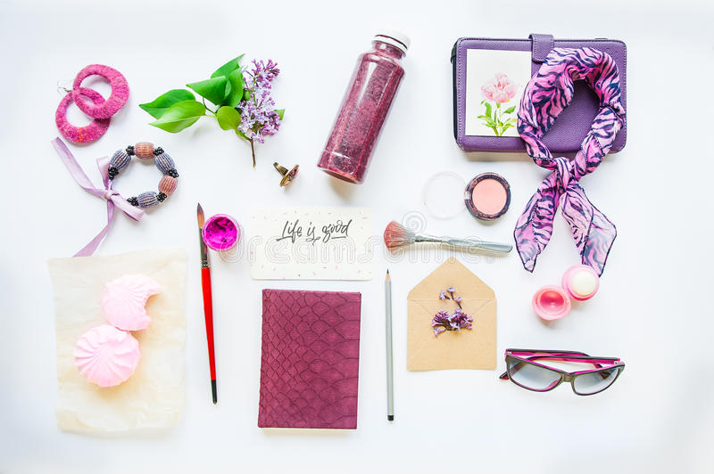 Beauty blog concept. Lilac colour. Female styled accessories: notebook, sunglasses, bijouterie items, cosmetics and lilac flowers royalty free stock images