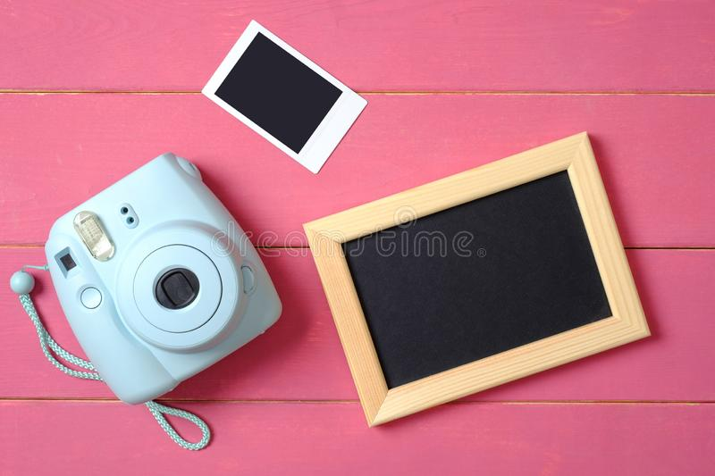 Beauty blogger accessories. Modern polaroid photo camera, picture frame and image on pink wooden background. Top view, flat lay. Composition, overhead stock photos