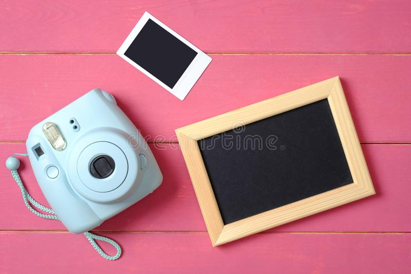 Beauty blogger accessories. Modern polaroid photo camera, picture frame and image on pink wooden background. Top view, flat lay. Composition, overhead royalty free stock photo