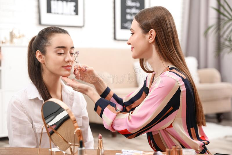 Beauty blogger doing model`s makeup stock image