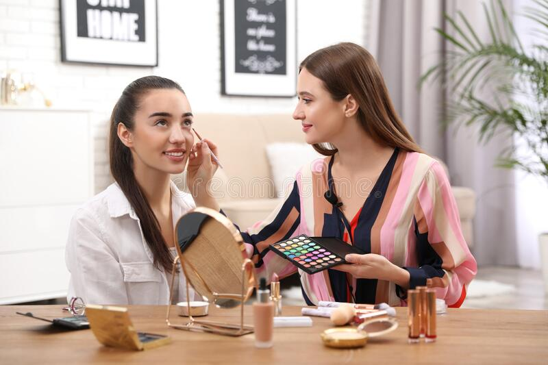 Beauty blogger doing model`s makeup royalty free stock photography