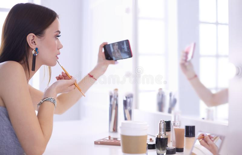 Beauty blogger filming makeup tutorial with smartphone in front of mirror stock photo