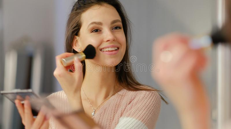 Beauty blog natural style makeup girl apply blush. Beauty blogger. natural style makeup. young beautiful girl applying blush in front of the mirror royalty free stock image