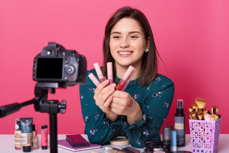 Beauty blogger sits in front of camera and advertising diferent lipsticks for followers. Online translation of tutorial video. stock image