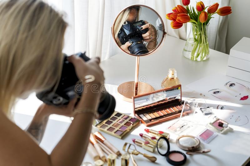 Beauty blogger taking photo of cosmetics royalty free stock images