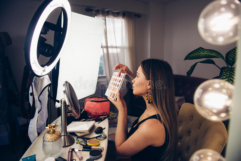 Beauty blogger woman showing cosmetics and telling makeup turtorial and taking video on camera royalty free stock image
