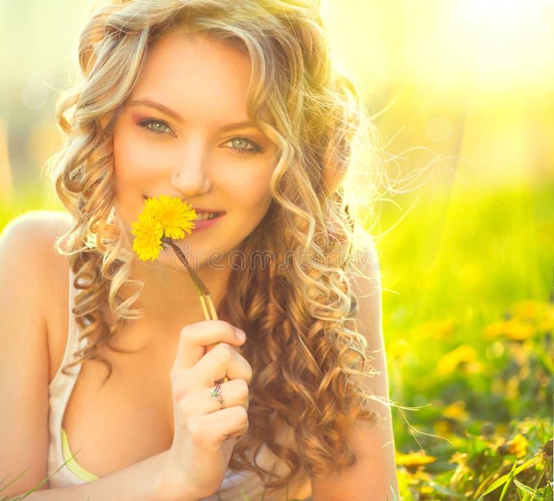 Beauty blond model girl smelling dandelion. Flower stock images