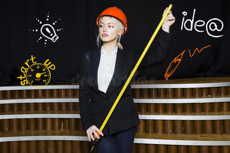 Beauty blonde businesswoman with designer or architect staff is standing against concrete wall with startup sketch on it. Concept of project launch royalty free stock photography
