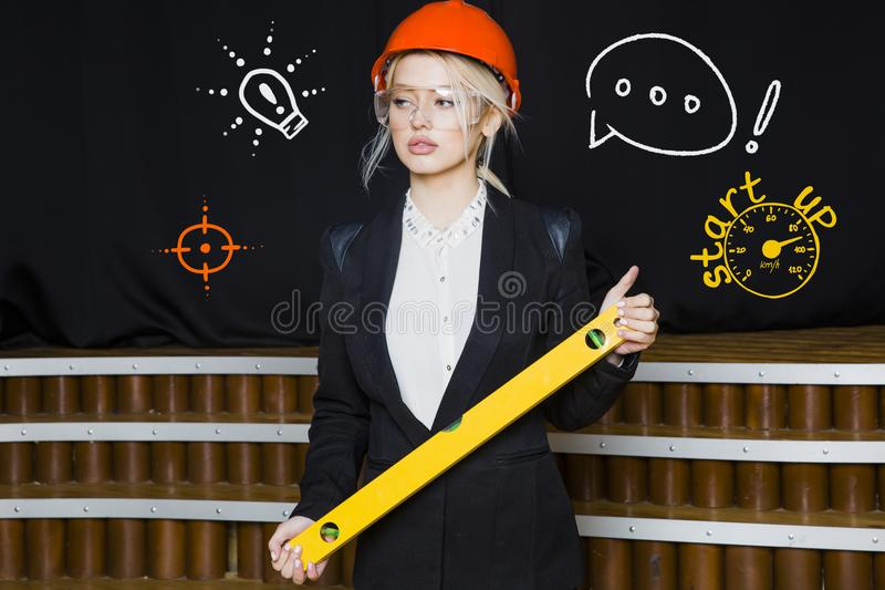 Charming Beauty Blonde Businesswoman With Designer Or Architect Staff Is Standing  Against Concrete Wall With Startup Sketch On It. Concept Of Project Launch.