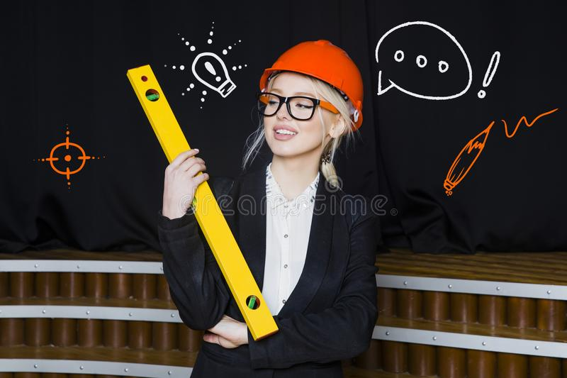 Beautiful Beauty Blonde Businesswoman With Designer Or Architect Staff Is Standing  Against Concrete Wall With Startup Sketch On It. Concept Of Project Launch.