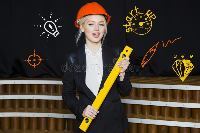 Attractive Beauty Blonde Businesswoman With Designer Or Architect Staff Is Standing  Against Concrete Wall With Startup Sketch On It. Concept Of Project Launch.