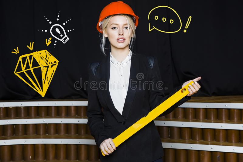 Beauty blonde businesswoman with designer or architect staff is standing against concrete wall with startup sketch on it. Concept of project launch stock image