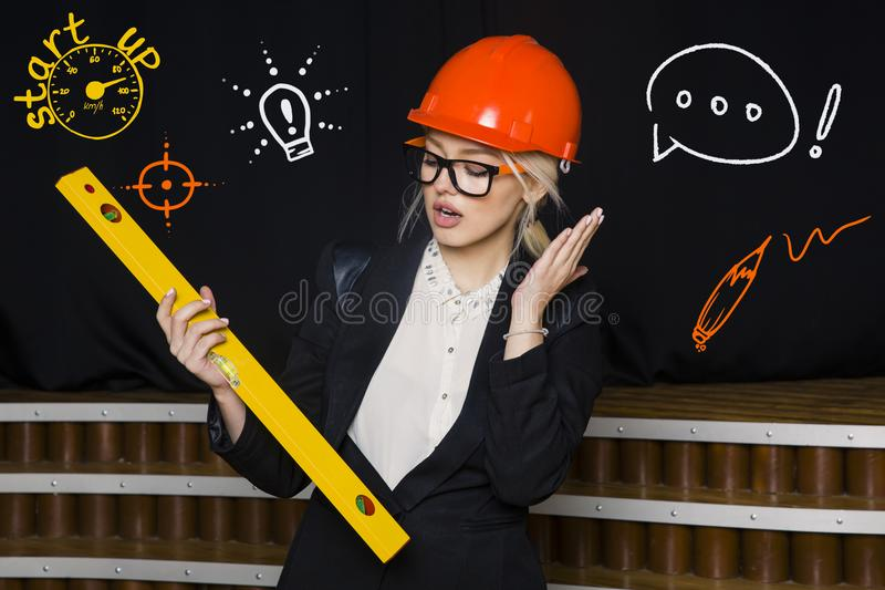 Beauty Blonde Businesswoman With Designer Or Architect Staff Is Standing  Against Concrete Wall With Startup Sketch On It. Concept Of Project Launch.