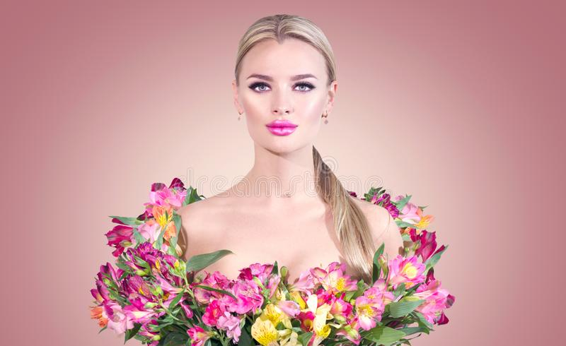 Beauty blonde model girl in summer dress made from colorful fresh flowers. Beautiful spring young romantic woman. Posing with Alstroemeria flowers stock photos