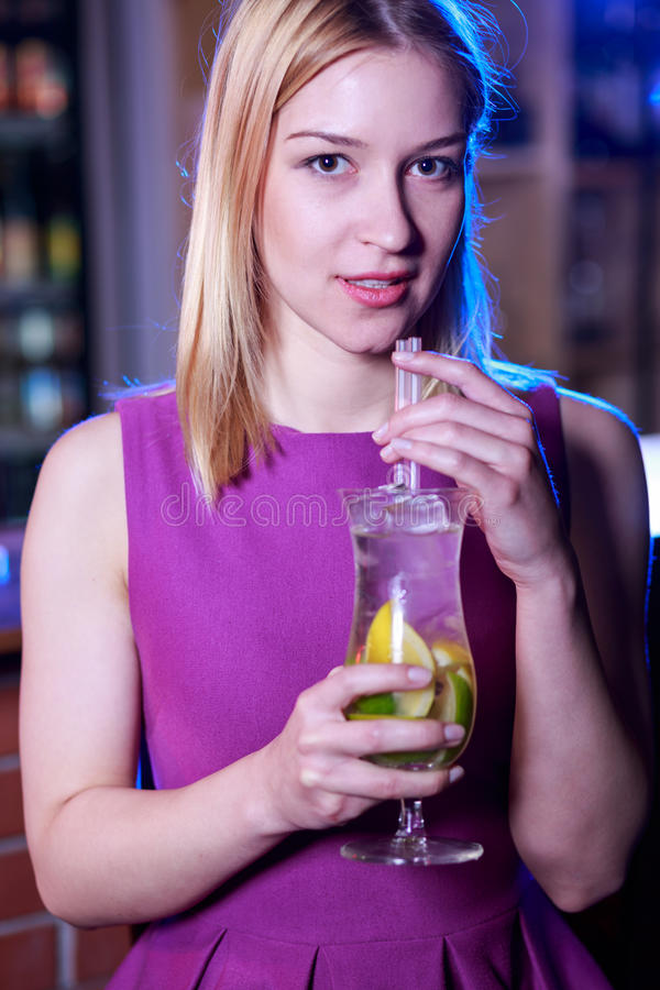 Beauty blonde woman drinking cocktail. In the bar royalty free stock photo