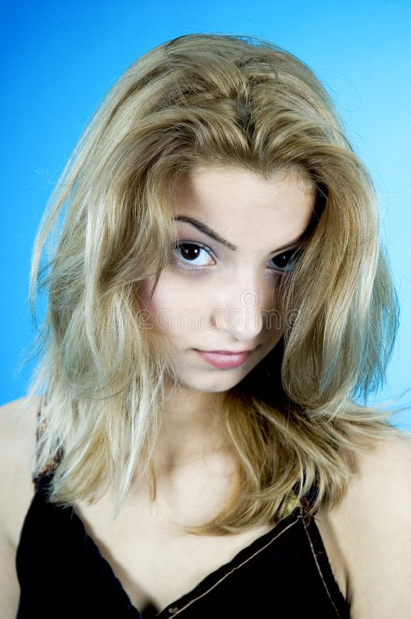 Beauty On Blue. Portrait of a blond young woman with hair falling toward her face. Taken in studio with a blue background royalty free stock photos