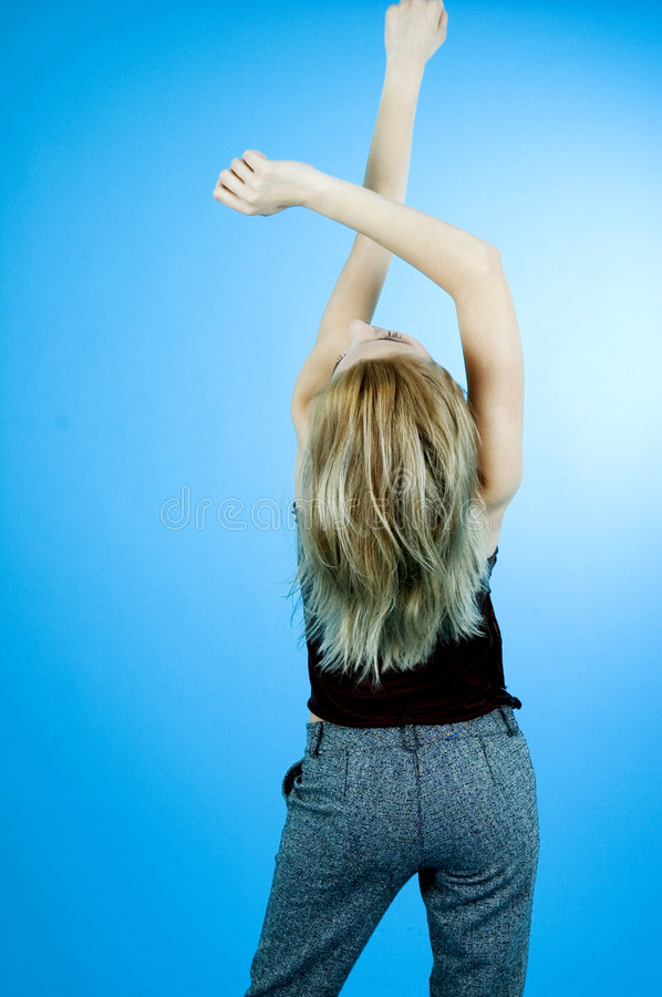 Beauty On Blue 9. Young woman from back view with arms crossed above her head. Taken in studio with blue background royalty free stock images