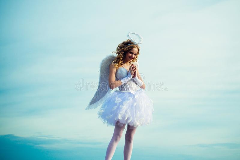 Beauty blue her eyes - charming lady in the heaven sunlight. Portrait of a cupid little girl pray. The God of Love. Cute stock photo