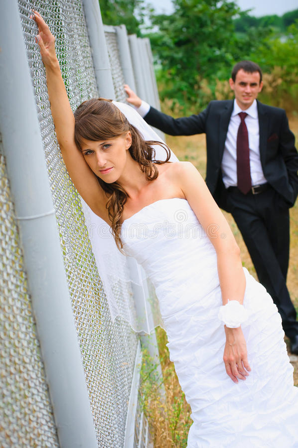 Beauty bride in white dress standing near fence. Groom behind stock image