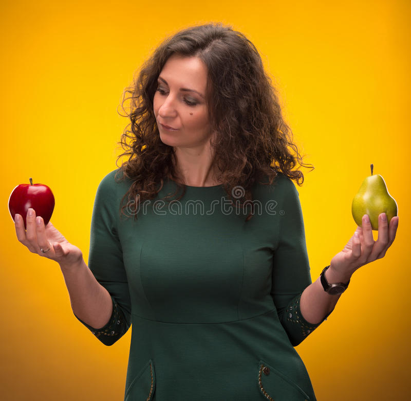 Beauty brunette with apple and pear royalty free stock photos